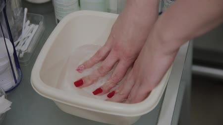 sulu : The process of preparing wet wipes for wiping the skin. Hands of a beautician close up. Aqueous solution in a white cup. Cosmetic procedure in the beauty salon Stok Video