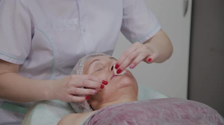 чистый : Beautician removes makeup to an elderly woman in a cosmetology clinic.