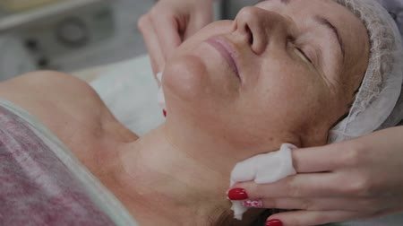 arcszín : Beautician performs the procedure of washing the face of an elderly woman in a cosmetology clinic. Stock mozgókép
