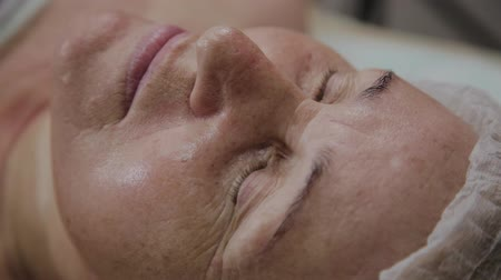 cosmético : An elderly woman is lying on a couch in a cosmetology clinic.