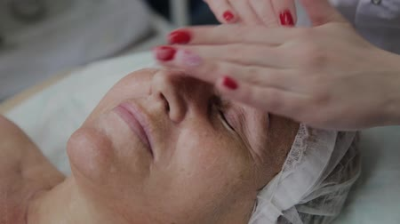 operacional : Female cosmetologist doing face massage to elderly woman in cosmetological clinic.