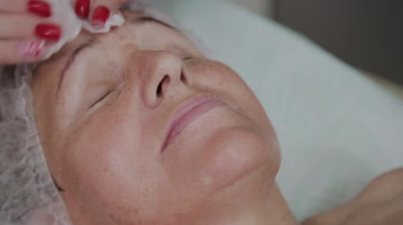 verwijderen : Beautician performs the procedure of washing the face of an elderly woman in a cosmetology clinic. Stockvideo