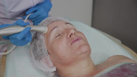 mimos : Professional cosmetologist performs the procedure for an elderly woman with microcurrents in the cosmetology office. Stock Footage