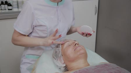 mezoterapia : Professional cosmetologist applies protective cream to the elderly woman in the beauty parlor.