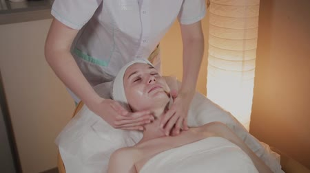 soyulması : Professional cosmetologist applies massage cream to the body of a young girl in the beauty salon.