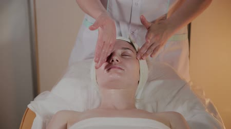 terapeuta : Professional beautician makes a complex massage to a young girl in the cosmetology office. Wideo