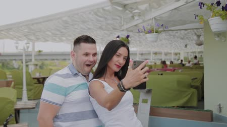 veranda : A beautiful woman and a cheerful man take a selfie on the veranda of the restaurant. Dostupné videozáznamy