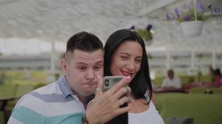 fotografando : A beautiful woman and a cheerful man take a selfie on the veranda of the restaurant. Vídeos