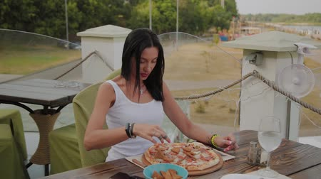 cheese slice : Fresh pizza on the table, a woman is preparing to eat it.