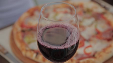 servido : A glass of red wine on the table against the background of fresh pizza. Vídeos
