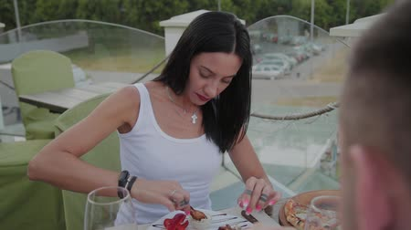 nibble : A woman enjoys eating fried chicken wings in a restaurant on the open terrace. Stock Footage