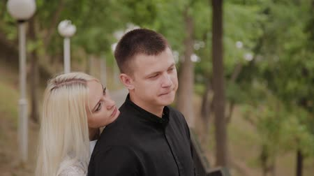 молодой взрослый человек : Happy couple in love stands on the descent in the park under the trees.