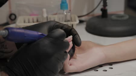 küfelik : Professional manicurist man removes old nail polish from a girl using a special nail polish remover.