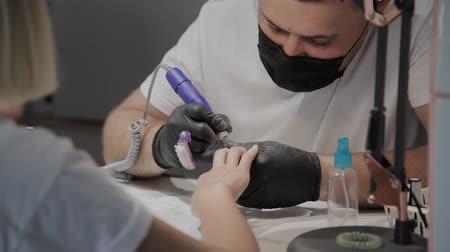 ferragens : Professional manicurist man removes old nail polish from a girl using a special nail polish remover.