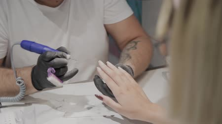 uñas rojas : Professional manicurist man removes old nail polish from a girl using a special nail polish remover.