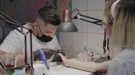 резать : Professional manicurist man removes cuticles with special scissors.