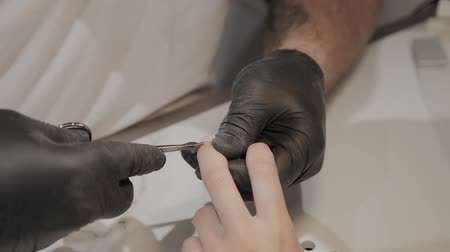 lakier do paznokci : Professional manicurist man removes cuticles with special scissors.