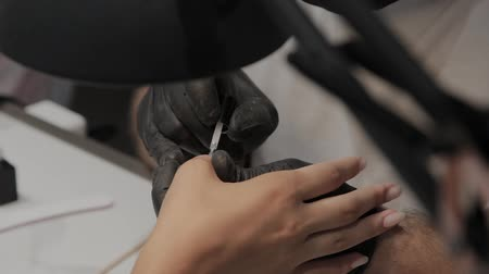 flacon vernis à ongle : Professional manicurist man varnishes a girls nails.