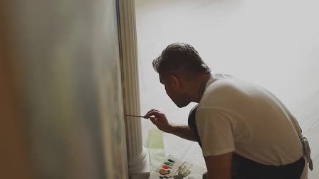 граффити : Professional artist paints a picture on the wall in the apartment.