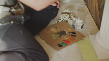 мольберт : Artist mixes paints on the palette before painting a picture, painter at the studio, creator makes piece of art.