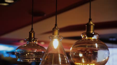 kőműves : Vintage and retro yellow light bulb hanging over dark background in cafe at night. Many luxury light lamp decorative industrial loft style in bistro and restaurant. Stock mozgókép
