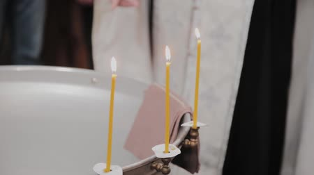 посвящение : Fonts for the baptism of babies with burning candles in the Orthodox Church. Стоковые видеозаписи