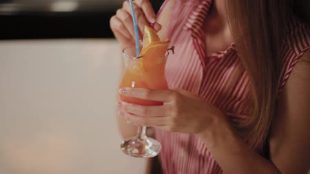 limonada : Beautiful girl with a beautiful fresh bright bright evening cocktail in a cafe. Stock Footage