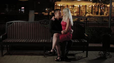 spolu : Happy couple of lovers on a bench in the evening on an alley in the city. Dostupné videozáznamy