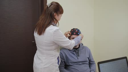 сканер : The doctor puts on a man a headset for the study of the human brain.