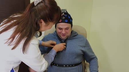 consciência : The doctor puts on a man a headset for the study of the human brain.