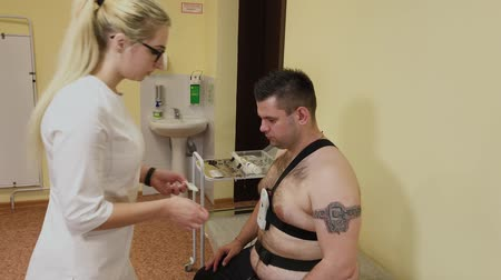 heart monitor : To a patient in a clinic, a male nurse puts a device on his body to study body parameters. Stock Footage