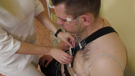 hastalık : To a patient in a clinic, a male nurse puts a device on his body to study body parameters. Stok Video