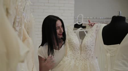 trouwen : Beautiful girl chooses a wedding dress in a bridal salon. Stockvideo