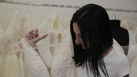 casar : Beautiful girl chooses a wedding dress in a bridal salon. Vídeos