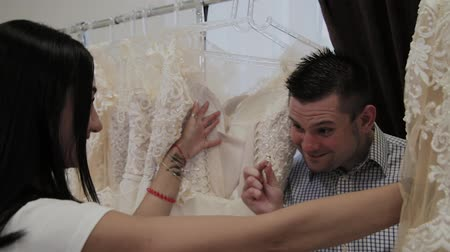 fitting : Beautiful girl chooses a wedding dress in a wedding salon, a man hides in dresses.