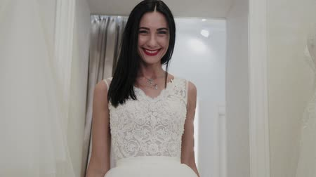 casar : Beautiful girl measures a wedding dress in a bridal salon. Vídeos