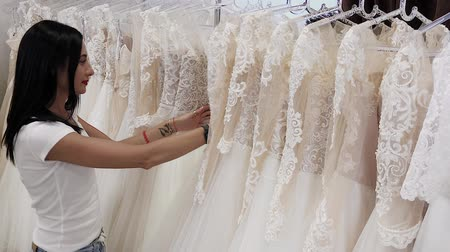 trouwen : Beautiful girl chooses a wedding dress in a wedding salon, a man hides in dresses.