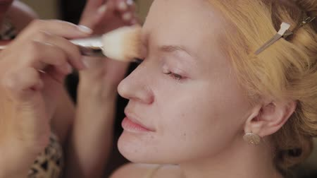 contorno : Professional make-up artist applies make-up photo of model to woman. Stock Footage