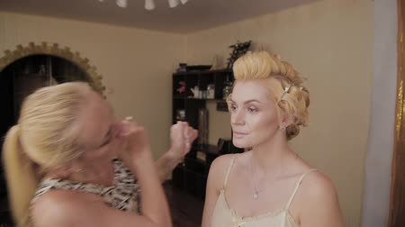 contornos : Professional make-up artist applies make-up photo of model to woman. Vídeos