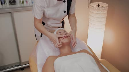 mimos : Woman doing facial massage at the spa salon. Stock Footage