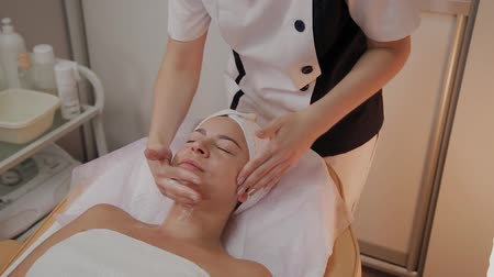 guance : Spa woman facial Massage. Face Massage in beauty spa salon. Female enjoying relaxing face massage in cosmetology spa centre. Body care, skin care, wellness, beauty treatment.