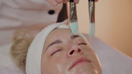 clay mask : Professional beautician applying mask with brushes on woman face.