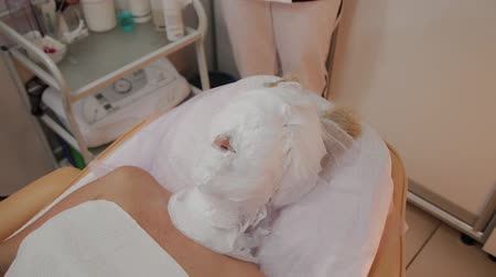 глина : Cosmetic procedure. Woman in beauty salon with mask on her face. Face mask application.