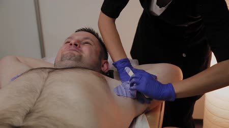 depilacja : Professional beautician makes waxing to a man in a beauty parlor.