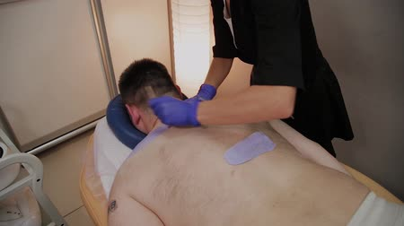 epilating : Professional beautician makes waxing to a man in a beauty parlor.