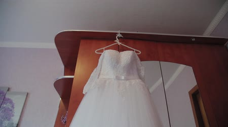 vállfa : Beautiful wedding dress hanging on a hanger in the room. Stock mozgókép