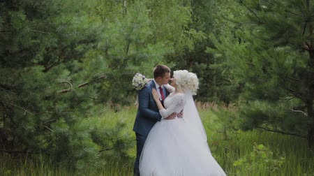 букет : Very beautiful bride and groom hold hands and hug in the forest. Стоковые видеозаписи