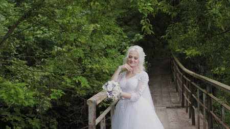 závazek : Beautiful blonde bride on a bridge near the railing in the forest.