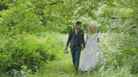çiçekler : Very beautiful bride and groom hold hands and hug in the forest. Stok Video