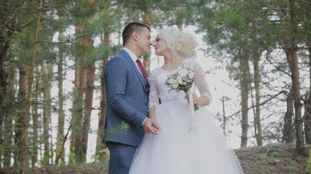 motyl : Very beautiful bride and groom hold hands and hug in the forest. Wideo